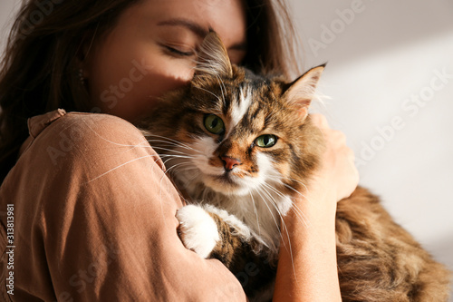 Photographie Portrait of young woman holding cute siberian cat with green eyes