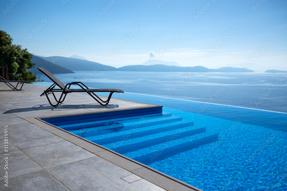 Fototapeta Infinity pool with chairs  With a view of the sea