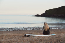 Rear View Of Thoughtful Woman Wearing Wetsuit On Surfing Staycation Looking Out To  Sea At Waves