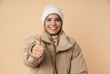 Portrait Of Happy Young Woman Showing Thumb Up And Smiling