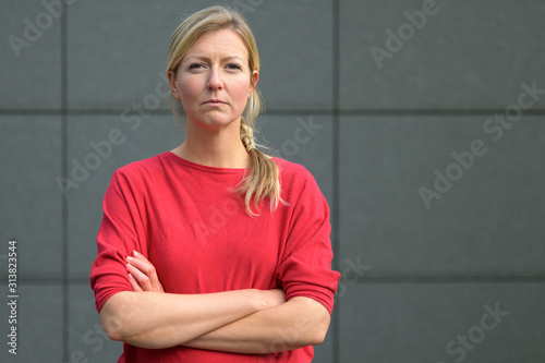 Fényképezés Blond woman in red shirt with arms folded