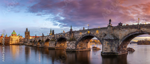 Obraz Prague, Czech Republic - Panoramic view of the world famous Charles Bridge (Karluv most) and St. Francis Of Assisi Church on a winter afternoon with beautiful purple sunset and sky - fototapety do salonu