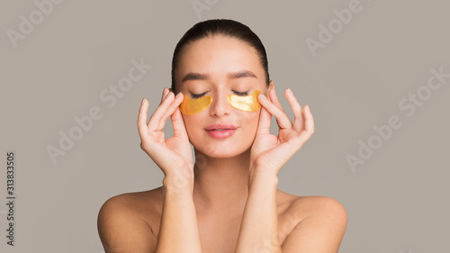 Fotografiet Young woman applying golden collagen patches under eyes