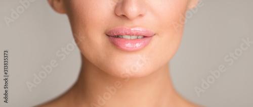 Fotografia Lip augmentation. Woman with plump lips over gray background