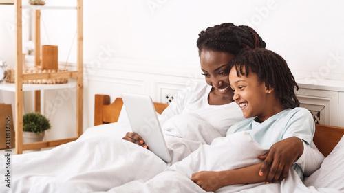 African american family watching comedy in bedroom Fototapeta