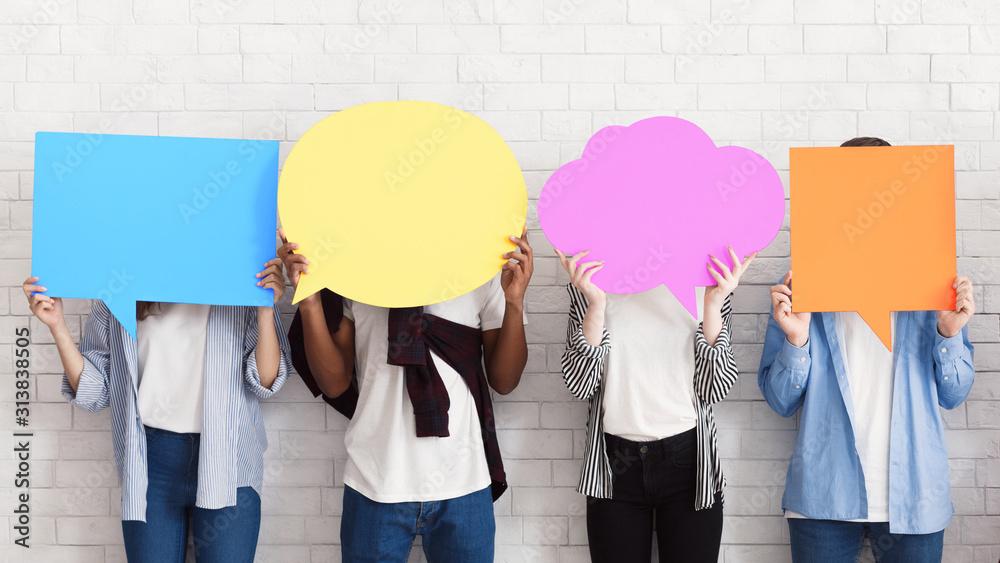 Fototapeta Sharing ideas. Teens holding empty speech bubbles