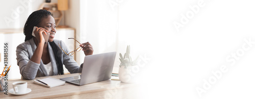 Smiling black female entrepreneur talking on cellphone in modern office
