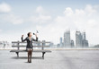 Business woman with megaphone sitting on wooden bench
