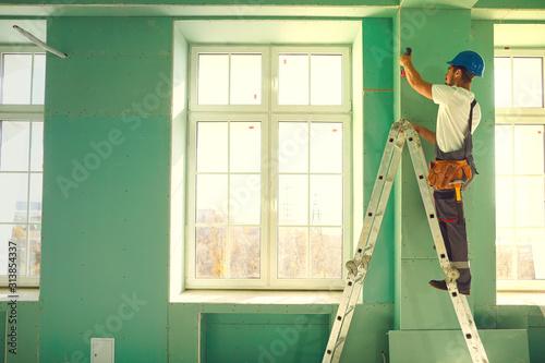 Obraz Worker builder installs plasterboard drywall at a construction - fototapety do salonu