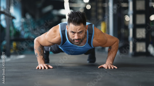 Strong guy making plank or push ups exercise Wallpaper Mural