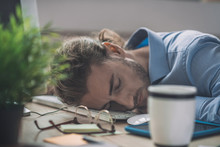 Young Bearded Man In Blue Shirt Having A Nap At Work