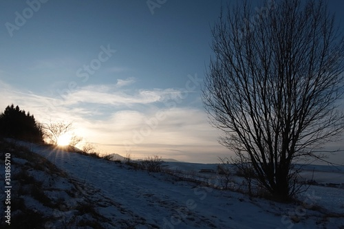 Sunset above winter snowy road and countryside with agricultural fields under Low Tatras mountains, Northern Slovakia Fototapeta