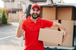 Image of a delivery man standing with parcel box and showing ok sign