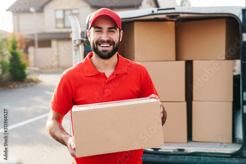 Obraz Image of smiling young delivery man standing with parcel box - fototapety do salonu