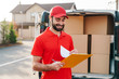 Image of cheerful delivery man holding clipboard and writing