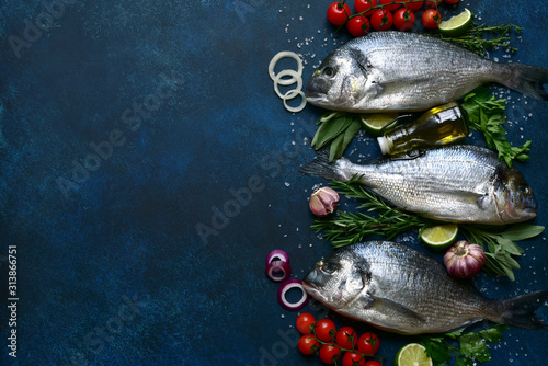 Obraz na plátně  Raw dorado fish with ingredients for making : tomato, citrus, herbs, garlic, olive oil and salt