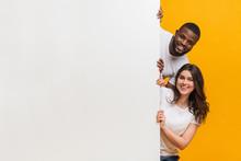 Joyful Interracial Couple Peeking From Behind White Advertisement Board