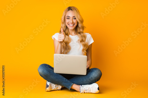 Cheerful woman using laptop and showing thumb up Wallpaper Mural