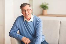 Elderly Gentleman Smiling Sitting On Sofa At Home