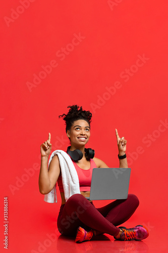 Valokuvatapetti Excited fitness girl with laptop pointing up at copy space