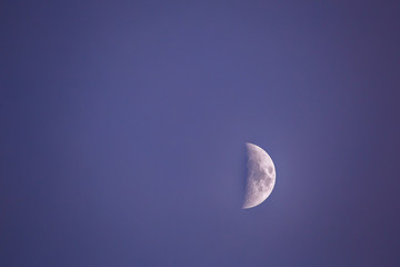 Moon with craters on a blue sky