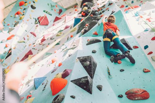 Teenager boy at indoor climbing wall hall Wallpaper Mural
