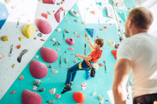 Father And Teenager Son At Indoor Climbing Wall Hall. Boy Is Hanging On The Rope Using A Climbing Harness And Daddy Belaying Him On The Floor Using A Belay Device. Happy Parenting Concept Image.