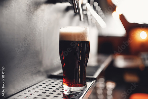 Obraz Light Draft cold beer pour in glass from crane in pub - fototapety do salonu