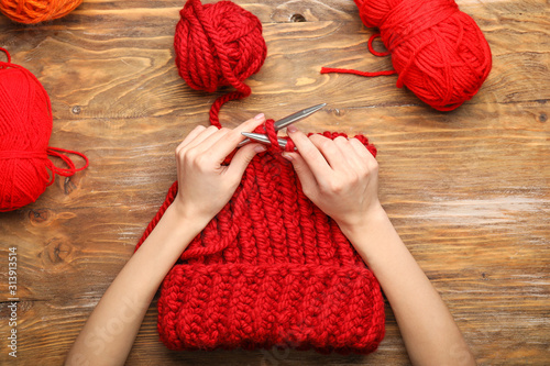 Obraz Young woman knitting warm hat at table, top view - fototapety do salonu