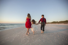 Kids Walking On The Beach Holding Hands At Christmas In Naples Florida