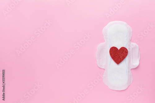 Obraz Menstrual pad with red heart on color background. Menstruation concept - fototapety do salonu