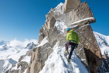 Rear View Of Man Climbing Rock...