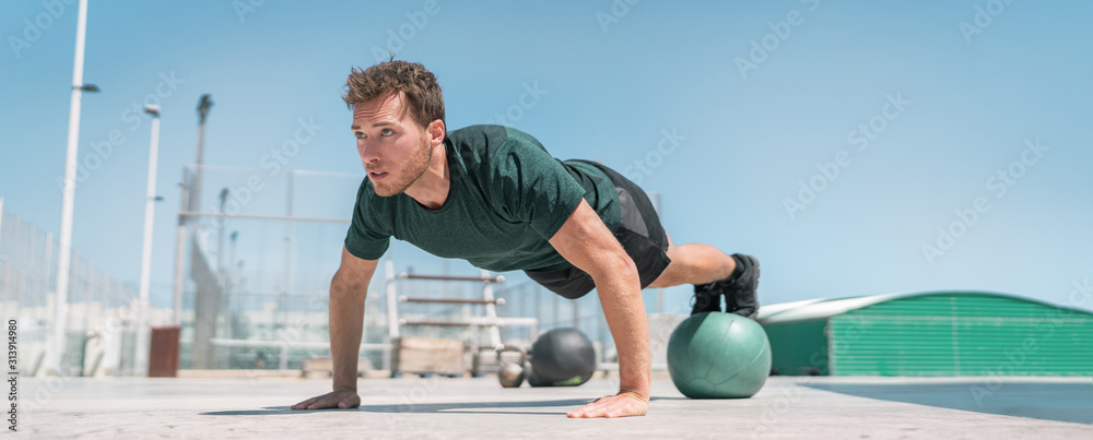 Fototapeta Fitness man banner panorama. Athlete strength training pushup balancing legs on medicine ball for advanced core body workout push-ups floor exercises at outdoor gym.