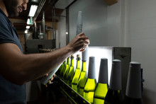 Man Placing White Foil Wrap On Bottles On Conveyor