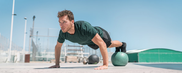 Fitness man banner panorama. Athlete strength training pushup balancing legs on medicine ball for advanced core body workout push-ups floor exercises at outdoor gym.