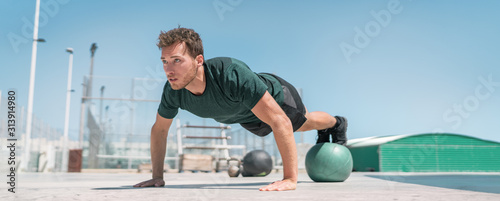 Fototapeta Fitness man banner panorama. Athlete strength training pushup balancing legs on medicine ball for advanced core body workout push-ups floor exercises at outdoor gym. obraz