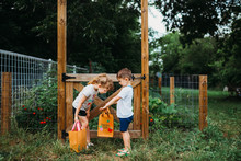 Boy Showing Vegetable Bag To His Sister He Picked From Home Garden