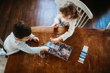 Young Brother And Sister Picking Beads To Making Bracelets At Home