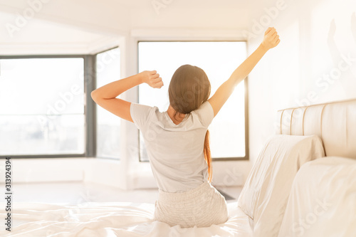 Obraz Morning woman waking up in bed in sunrise sunlight glow from window. Early bird happy girl in pajamas on weekend stretching arms. Healthy wake-up routine home lifestyle. - fototapety do salonu