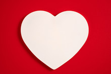 White Wooden Heart On A Red Background For Valentine's Day, Wedding And Other Holidays, View From The Top.