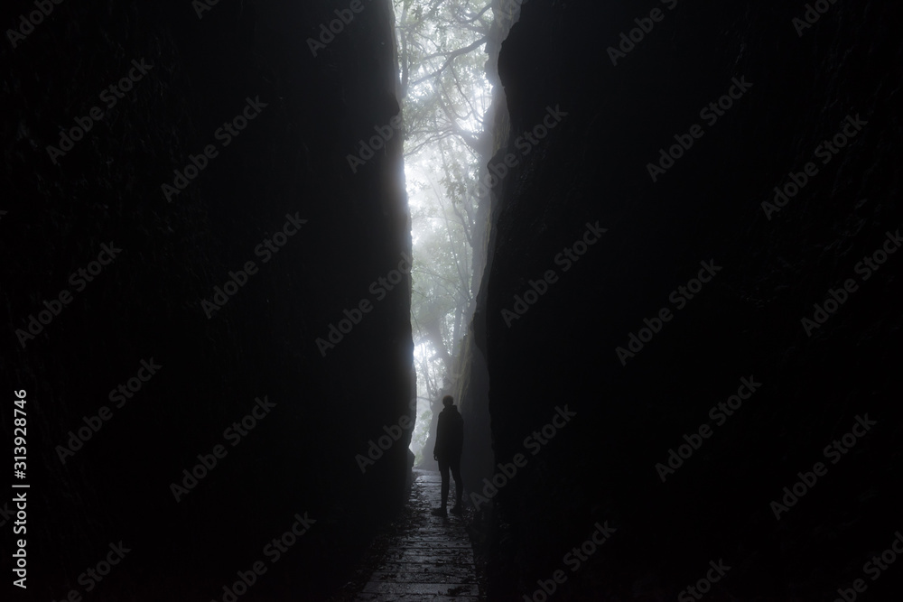 Fototapeta Silhouette of a tall unrecognisable woman looking out from a dramatic cleft in the rocks of the mountains of Madeira island. The light forms a V shape with a path passing through. Horizontal photo.