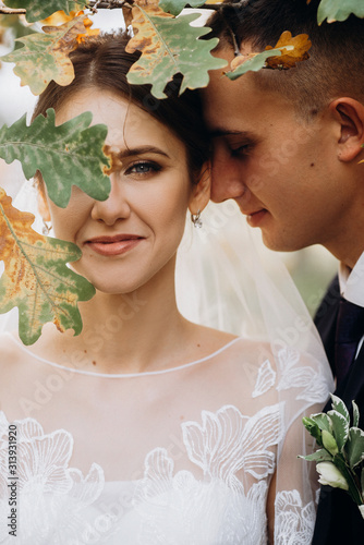 Cuadros en Lienzo Groom and Bride portrait with oak leaf before her face in autumn