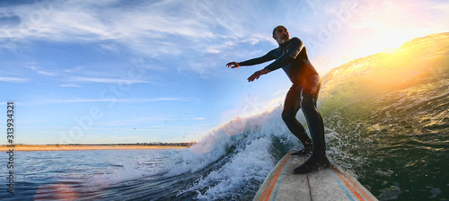 Foto  Mature senior adult surfing on a big wave in the ocean