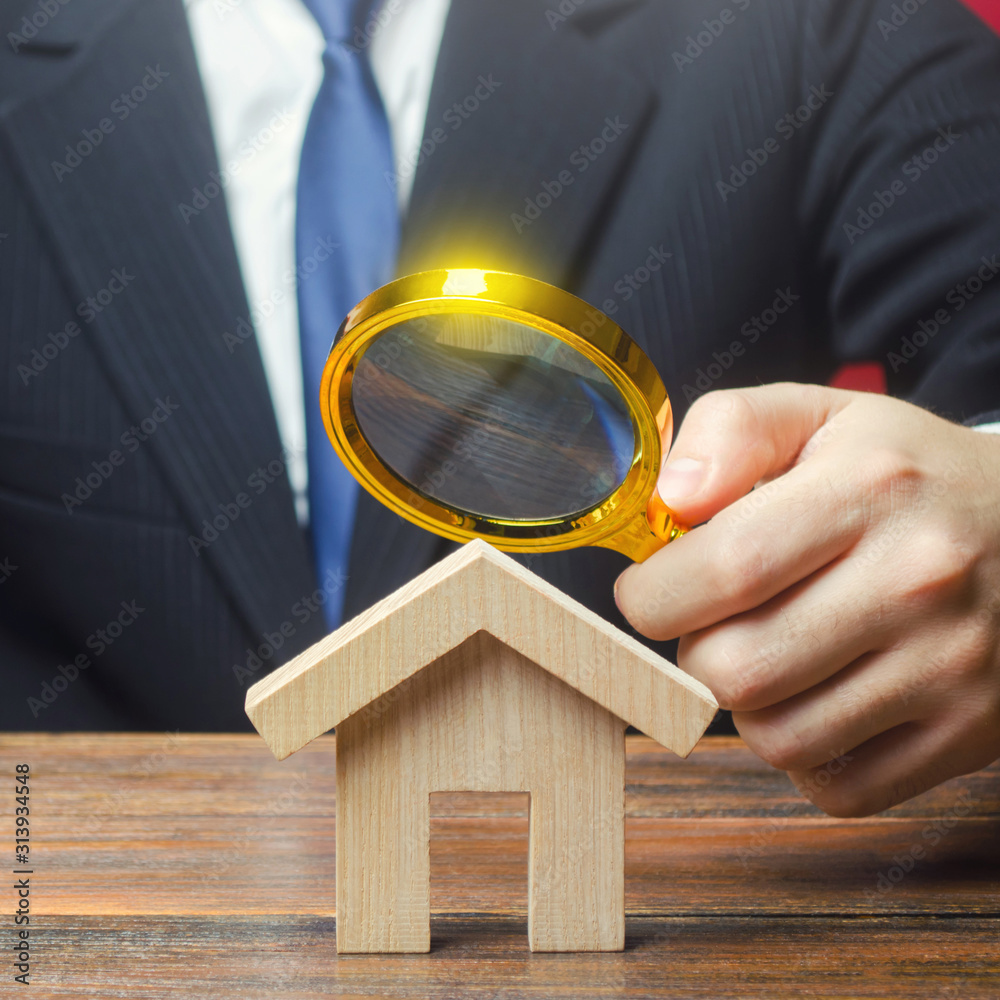 Fototapeta A man is studying a house through a magnifying glass. Fair value of real estate. Property valuation. Legal deal. Standards and quality of construction. Legality and transparency of purchase agreement.
