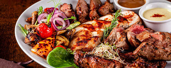 Turkish cuisine. Assorted different meat on the grill, lamb, chicken, pork with grilled vegetables. Serving dishes in a restaurant on a white plate. background image, copy space