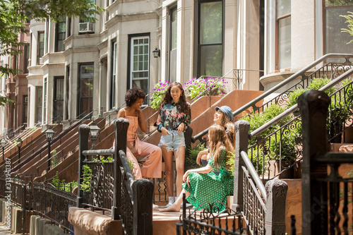 Happy female friends talking on steps against houses in city - 313941387