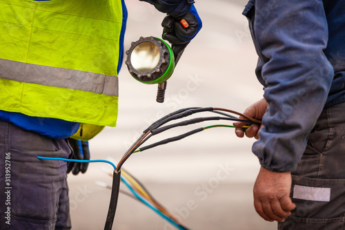 Fotografie, Tablou Electrical network and street light pole repair using heat shrink tubing