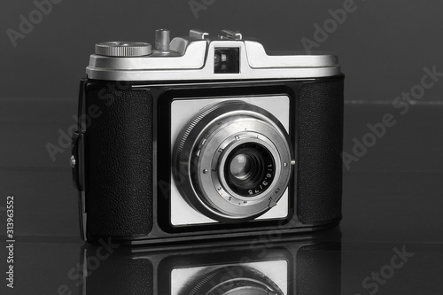 Fotografía Old retro photo camera on dark black table