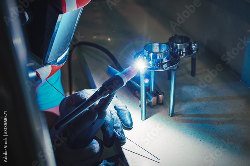 Photo Men's hands with argon welding machine