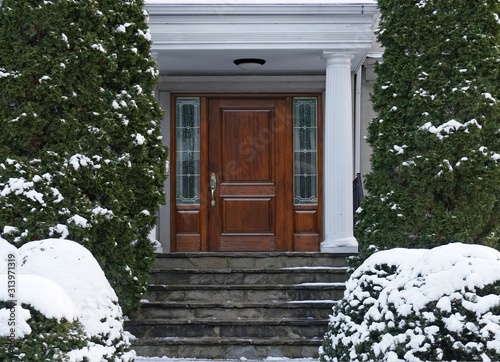 Fototapeta Elegant wooden front door of house with snow covered shrubbery